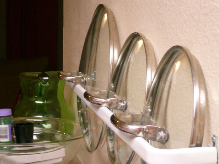 40+ Organization and Storage Hacks for Small Kitchens --> Organize pot lids with a towel rack