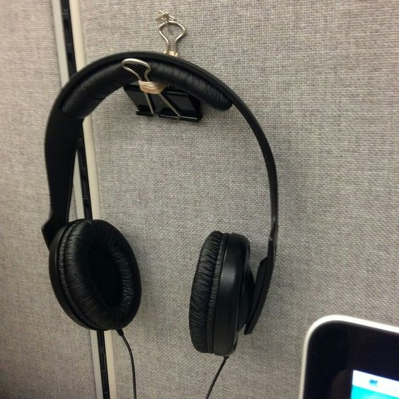 Make a headphone holder by twisting a rubber band around the two metal clasps and pinning the binder clip on the wall