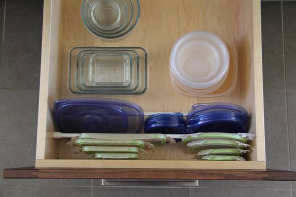 20+ Creative Uses of Tension Rods to Organize Your Home --> Use Tension Rod to Keep Plastic Lids in Place in the Drawer