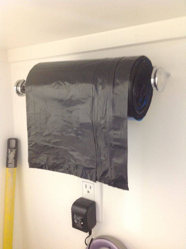 30+ Creative Ways to Organize Your Garage --> Use a paper towel holder as a dispenser for a large garbage bag roll