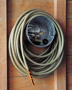 30+ Creative Ways to Organize Your Garage --> Store garden hose and sprinklers in a bucket hanging from the wall