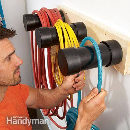 30+ Creative Ways to Organize Your Garage --> Build plastic pipe hangers to store electrical cords and hoses