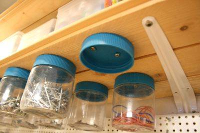 30+ Creative Ways to Organize Your Garage --> Mount the lids of recycled plastic jars to the bottom of wooden shelves and use them to store screws, nails and other small objects
