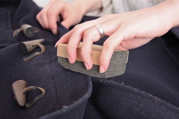 Get rid of lint balls on a coat using a pumice stone